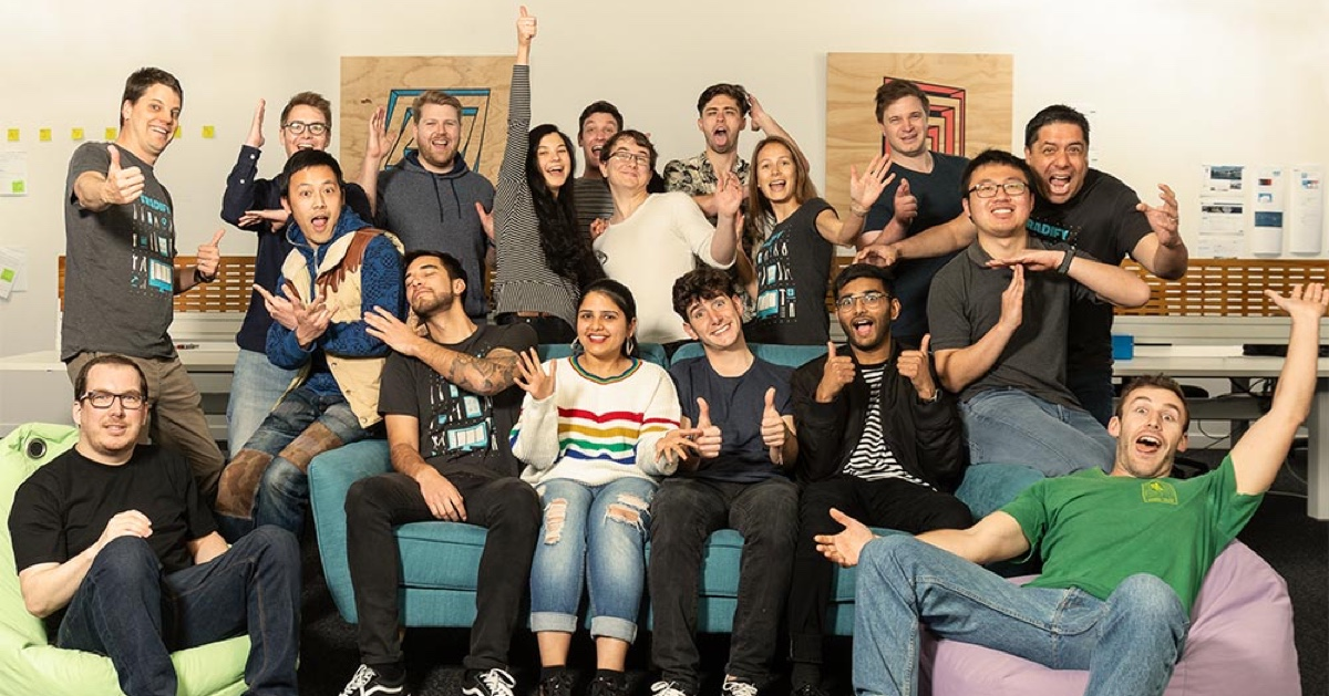 Photo of about 20 members of the Tradify team laughing and sitting around a couch