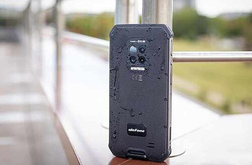 A black ulePhone splashed with water and perched on a ledge