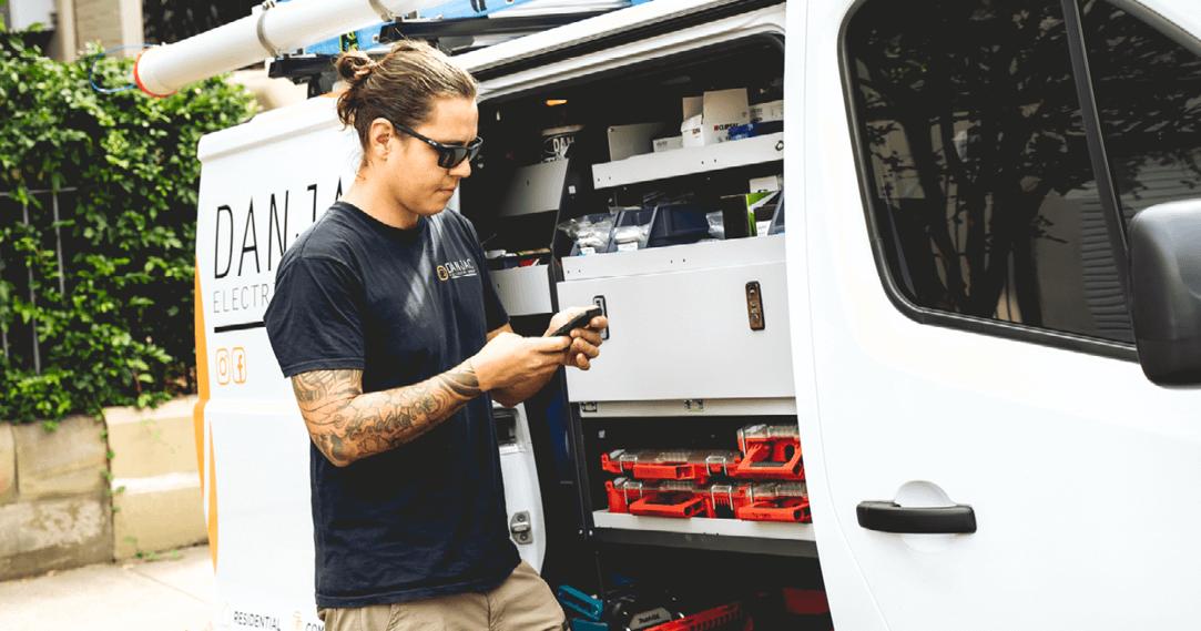 danjac electrical standing looking at his phone in front of his van