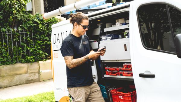 body image_danjac electrical on phone next to white van with milwaukee storage bins