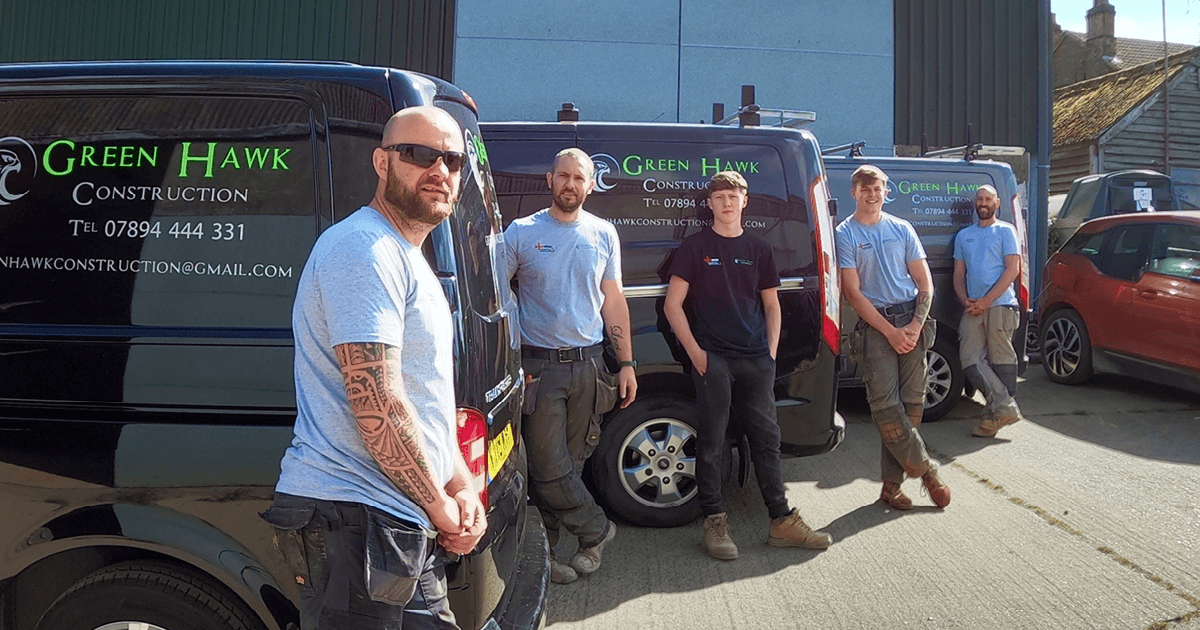 A photo of the Green Hawk construction team - 5 guys stand with 3 of their black vans.