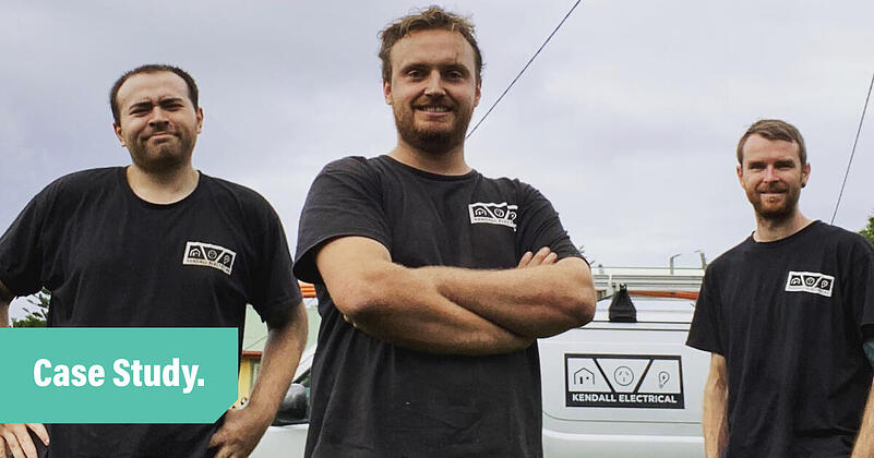 A photo of three electricians from the Kendall Electric team. Each guy wears a black t-shirt with the Kendall Electrical logo.