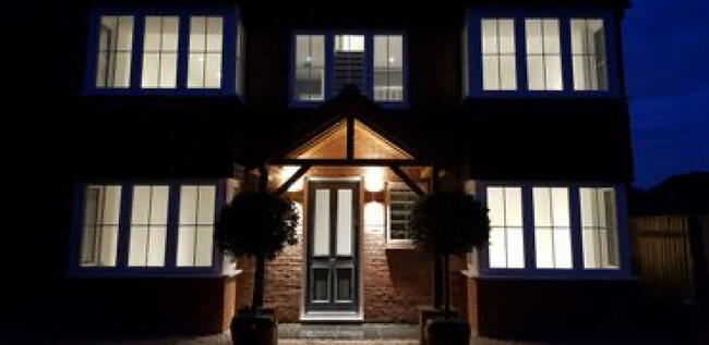 A photo of a brick house at night with brand new front porch lightning installed by Kennett Electrics