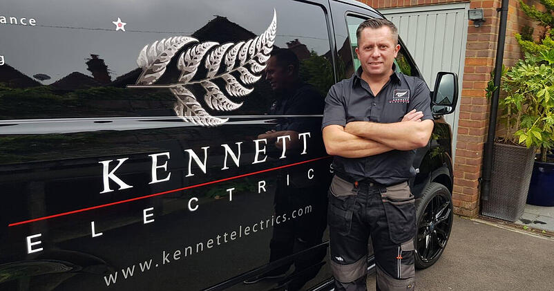 Tradify customer and electrician David Kennett stands proudly, arms folded in front of his black van sign written with his name and a silver fern