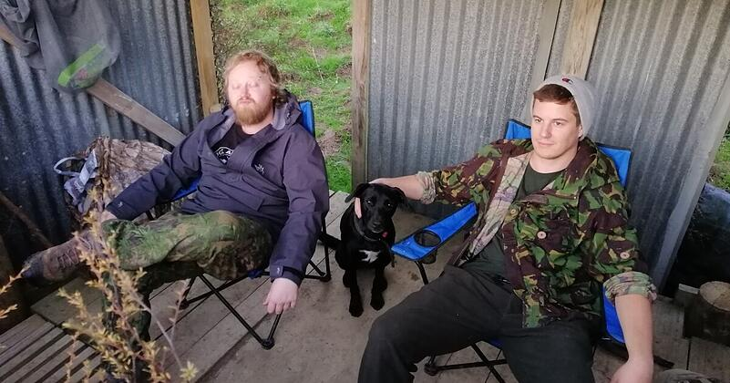 Andrew and friend relax in a shed