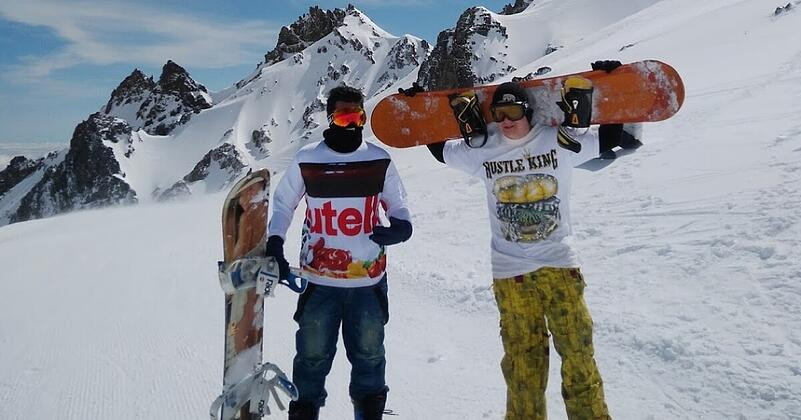 Two guys in snowboarding gear on a snow covered mountain