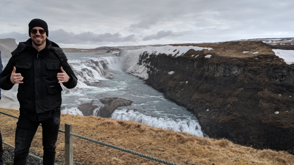 sam in iceland next to a waterfall