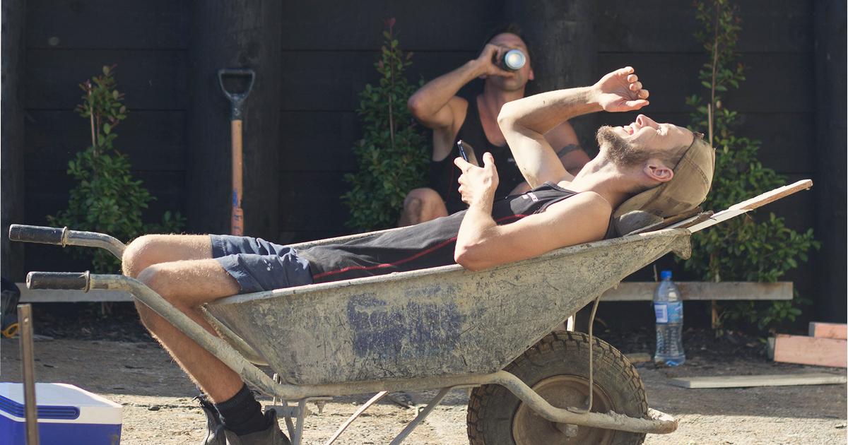 A landscaper lies in a dirty wheelbarrow, laughing