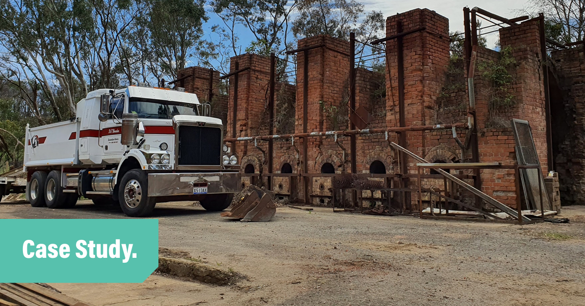A white dump truck parked in front of an old brick kiln with the words Case Study