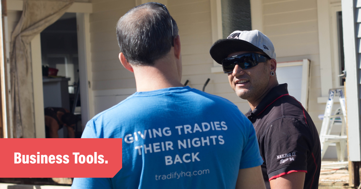 Two tradespeople talking on a job site