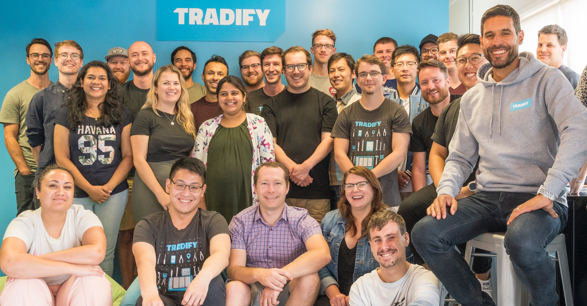 Tradify team photo - a large group of smiling, hard-working people