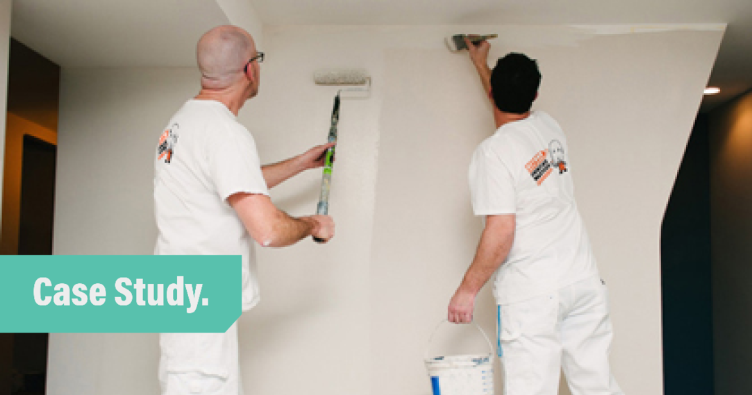 Two men in white overalls painting a wall white. One uses a brush and one uses a roller.
